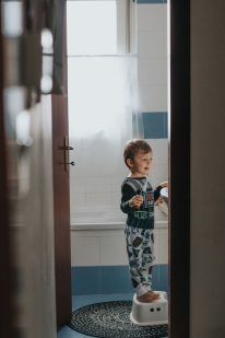 Toddler brushing teeth on stepstool with starters pjs.
