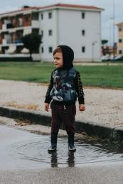 toddler playing in puddle fun, wearing rain boots.
