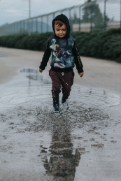 Toddler playing in puddle, wearing rain boots and star wars sweater.