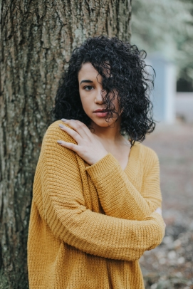 Forest portrait of girl with green eyes, curly hair and red sweater in the pacific northwest, PNW, Kitsap County. Silverdale, bremerton, port orchard, poulsbo, gig harbor, Bainbridge island, washinton state.